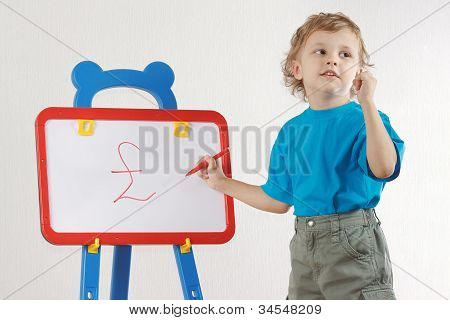 Little cute smiling boy drew a pound sign on the whiteboard