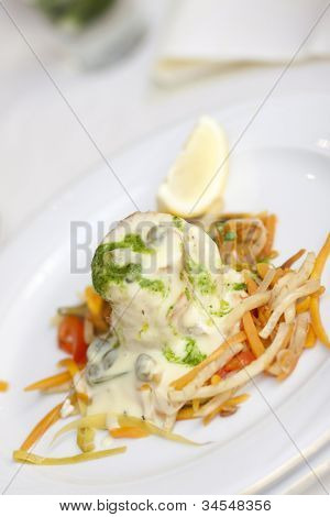 A fish dish with white fish fillet presented with butter sauce and vegetable