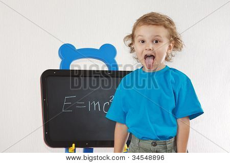 Little boy shows tongue as Einstein near formula on a blackboard