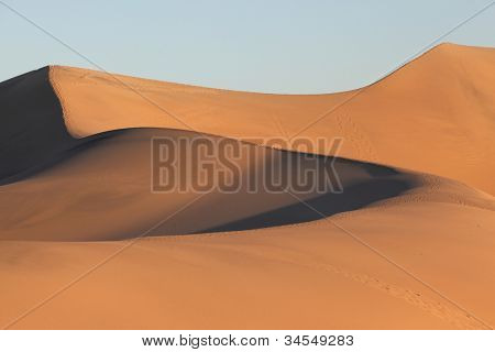 Clear graphic shapes of sand dunes at sunrise. California, Death Valley