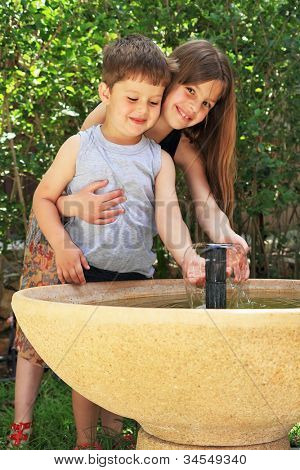 Two charming children on walk in park. Elder sister embraces the younger brother. They play in transparent water of a fountain with a round bowl.