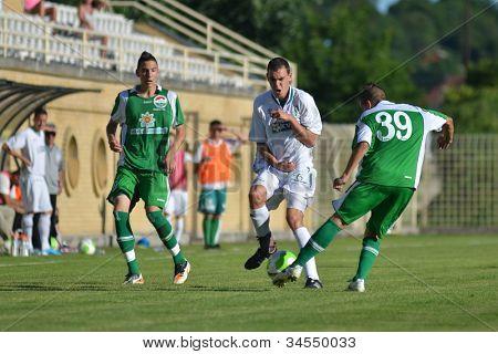 KAPOSVAR, HUNGARY - JUNE 16: Krisztian Kirchner (in white) in action at the Hungarian National Championship under 19 game Kaposvar (white) vs. Paks (green) on June 16, 2012 in Kaposvar, Hungary.