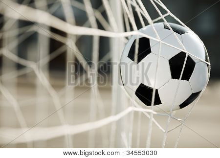 Soccer ball going into goal net ,selective focus