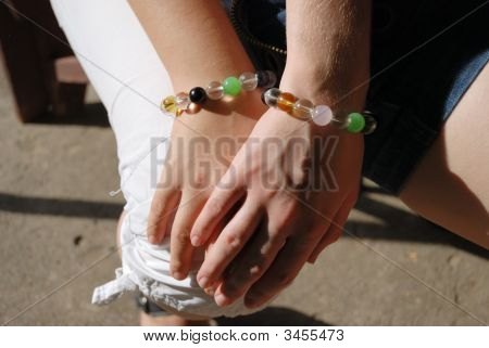 Hand Covered With Another Hand In Equal Bracelets