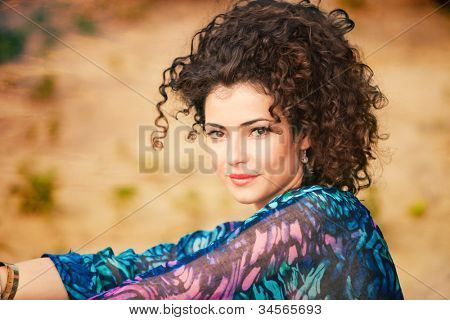 young smiling curly hair woman portrait outdoor shot summer day