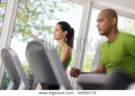 Young People Exercising And Running On Treadmill In Gym