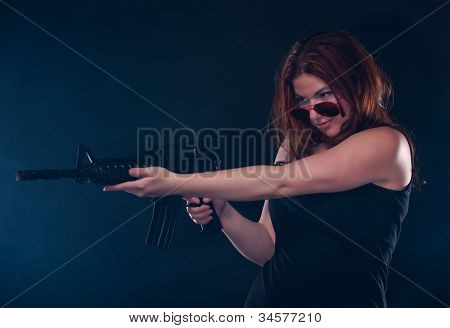 Woman looking over her glasses while aiming a gun