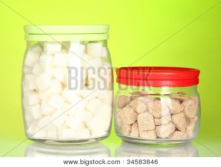 Jars with brown cane sugar lump and white lump sugar on colorful background