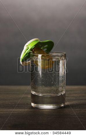 Bebê manequim com bebida alcoólica em fundo cinza