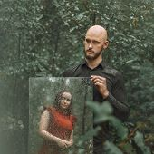 Young Guy Holds A Mirror In The Forest In The Rain. A Girl Is Reflected In A Mirror. Concept Of Rela poster