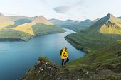 Lonely tourist in yellow jacket looking over majestic fjords of Funningur, Eysturoy island, Faroe Is poster
