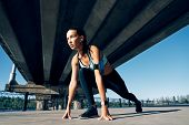 Runner Woman Ready To Run In Running Start Pose On The City Industrial Background. Sprinter Training poster