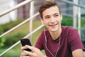 A smiling young man with a smartphone, in the street.  Happy teenage boy is using mobile phone, outd poster