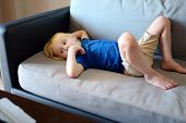 Little Boy Laying On Couch And Watching Cartoons By Tablet Pc. Kids And Gadgets. Addiction. Gadget-a poster