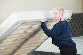 An Adult Stylish Woman With A Short-cut Blonde Chooses A Large Orthopedic Bed With A Lifting Mattres poster