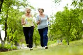 stock photo of environment-friendly  - Portrait of two senior females running outdoors - JPG