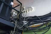 Lots Of Different Cables Hanging In A Mess On The Wall. Poor Cable Wiring. A Jumble Of Cables poster