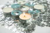 White Burning Candle With Silver Stars Around At The White Background, White Burning Candle With Blu poster