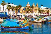 Traditional fishing boats in the Mediterranean Village of Marsaxlokk, Malta poster
