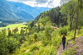 Alpine Landscape In Summer, Filisur, Switzerland. Young Woman Looks At Red Train Of Bernina Express  poster