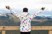 Happy Tourist Girl In Colored Jacket With Hands Up Standing On Observation Deck In Mountains Covered poster