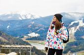 Happy Tourist Girl In Colored Jacket Standing On Observation Deck In Mountains Covered Snow poster