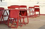 Foldable Red Table And Chair Set Placed Outdoors. Foldable Chairs, Leaning On The Table. Temporary T poster