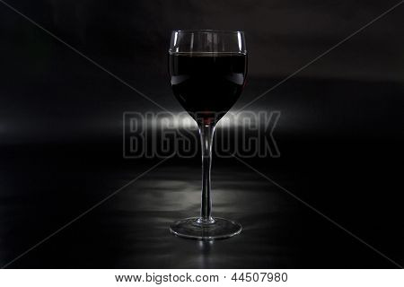 Glass of Wine Spotlighted on Reflective Black Background