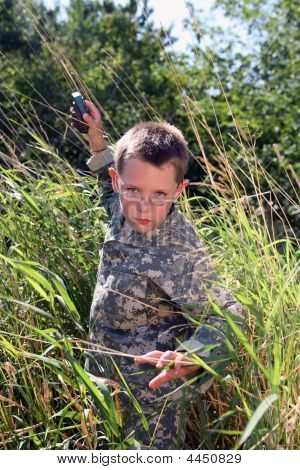 Boy In Camoflauge Raising Arm To Throw (pretend) Grenade