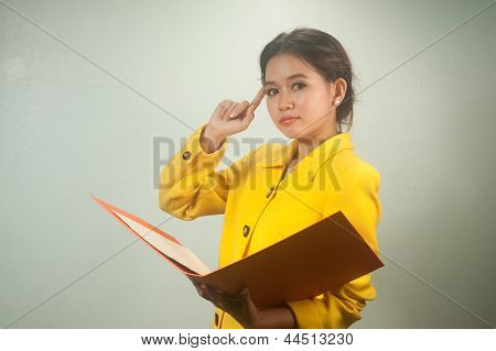 Pretty Asian Businesswoman Ruminated  And Holding A File .