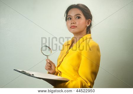 Pretty Young Asian Business Woman Looking Document By Magnifying Glass .