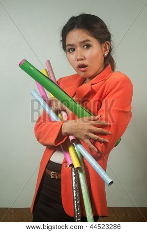 Busy Asian Business Woman With A Lot Of Colorful  Papers  On  Background .