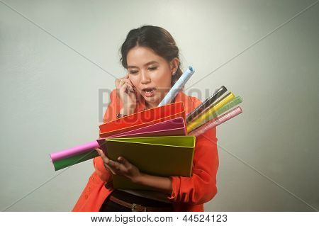 Busy Asian Business Woman With A Lot Of Folders And Colorful Papers ,calling By Phone On Background