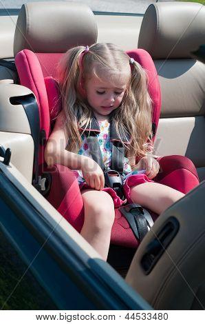 Little cute girl sitting in car seat