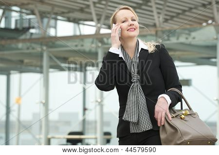 Portrait Of A Traveling Business Woman Talking On Mobile Phone