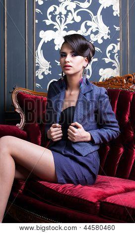 Elegant Girl Sitting On Red Luxury Sofa