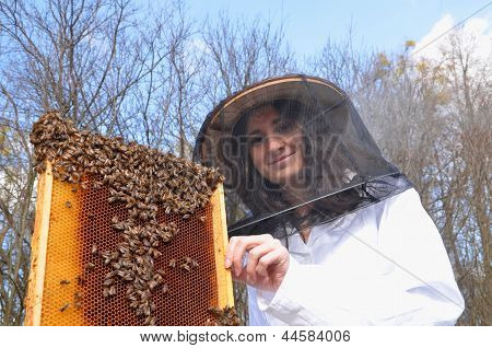 A young girl beekeeper in apiary