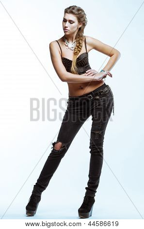 Young Blond Woman In Black Top And Jeans Posing On Light Background