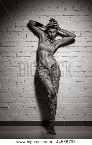 Nude Young Woman In Jeans Posing Studio On Background Of Wall Bricks
