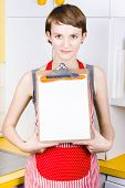 stock photo of pinafore  - Attractive woman wearing red pinafore standing in the kitchen holding a blank recipe board - JPG