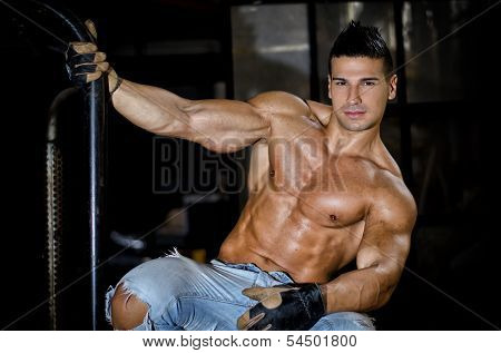 Muscular Latino Bodybuilder In Jeans Hanging From Metal Handle