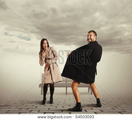 startled young woman looking at crazy man in coat on the street