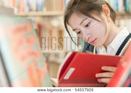 Student Reading A Book On Bookshelf