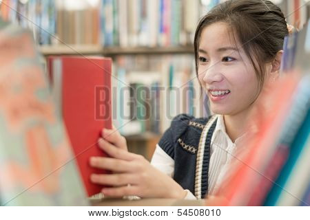 Girl Picking Out A Red Book