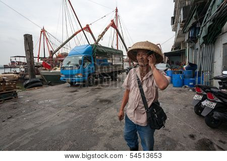 MACAU - OCTOBER 30: Businessman says on mobile phone in the fishing port on October 30, 2012 in Macau, China. Fishing industry provides internal needs Macao  products harvested in the sea.