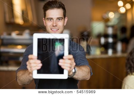 Portrait of male cafe owner holding digital tablet in restaurant