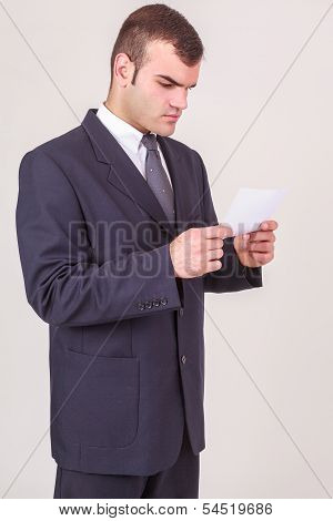 Businessman frowning as he reads a note