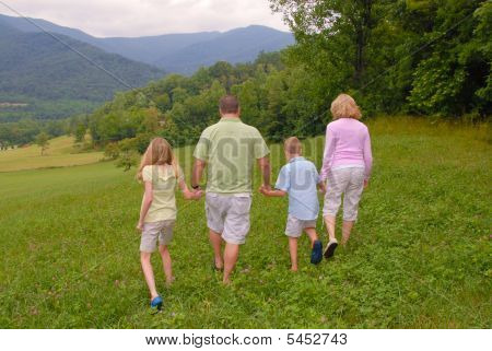Family of four walking in the woods