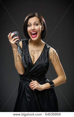 Half-length portrait of female singer wearing black evening dress and handing microphone on grey background. Concept of music and retro fashion