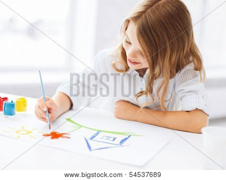 education, school, art and painitng concept - little student girl painting picture